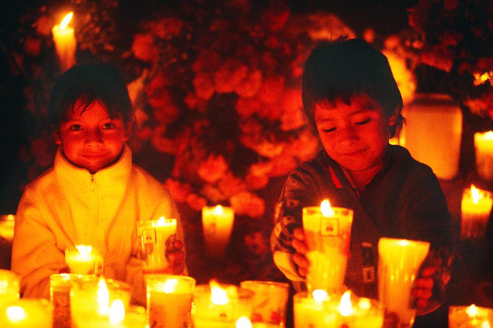 Children surrounded by candles and flowers, Night of the Dead (Noche de Muertos), November 1, Tzintzuntzan Cemetery, near Patzcuaro, Michoacan, Mexico