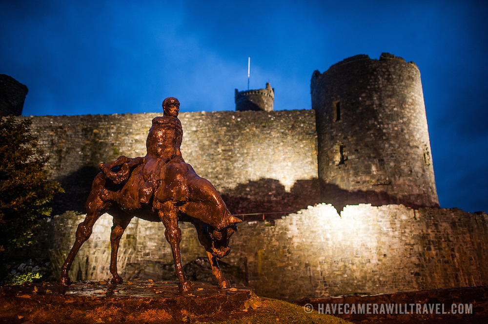 The Two Kings statue at Harlech Castle in northwestern Wales at dusk. Sculpted by Ivor Roberts-Jones and unveiled in 1984, the sculpture depicts the Mabinogion story of Branwen, a lament of the folly and carnage of war. In the sculpture, the figure of Bendigeidfran, bearing the body of his nephew Gwern, symbolises the sorrowful burden that love can be. Harlech Castle in Harlech, Gwynedd, on the northwest coast of Wales next to the Irish Sea, was built by Edward I in the closing decades of the 13th century as one of several castles designed to consolidate his conquest of Wales.