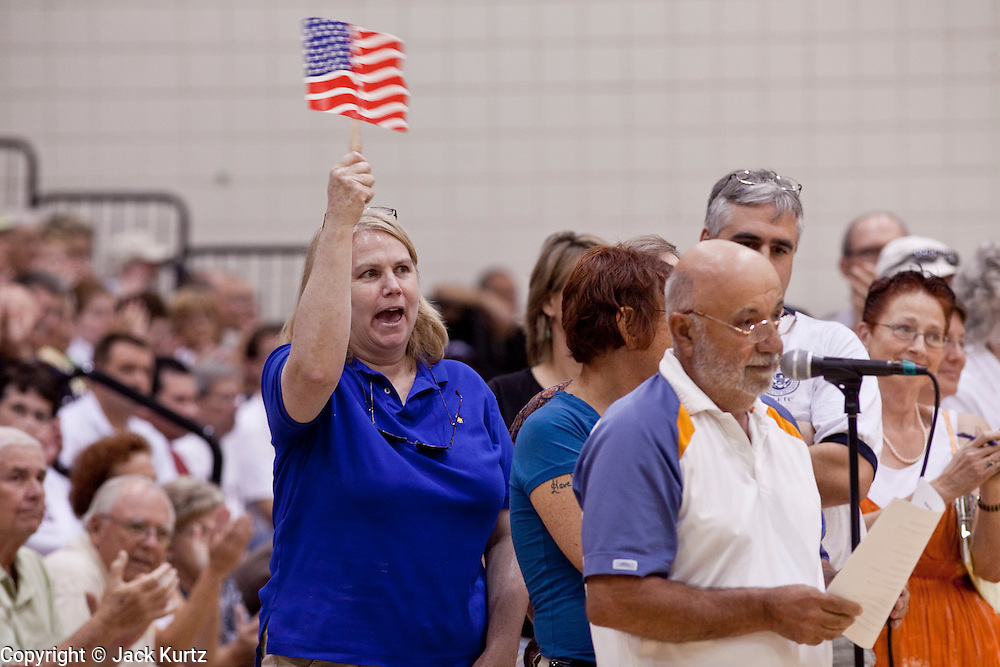 """Aug 10, 2009 -- CHANDLER, AZ: People, most opposed to health care reform, wave American flags during a town hall meeting on health care reform in Chandler, AZ. Rep. Jeff Flake, (R-AZ) hosted a """"town hall"""" style meeting on health care reform at Basha High School in Chandler Monday. Flake, a conservative Republican, has opposed President Obama on many issues, like the stimulus and health care reform. Protestors who have shut down similar meetings hosted by Democrats, gave Flake a warm welome.   Photo by Jack Kurtz / ZUMA Press"""