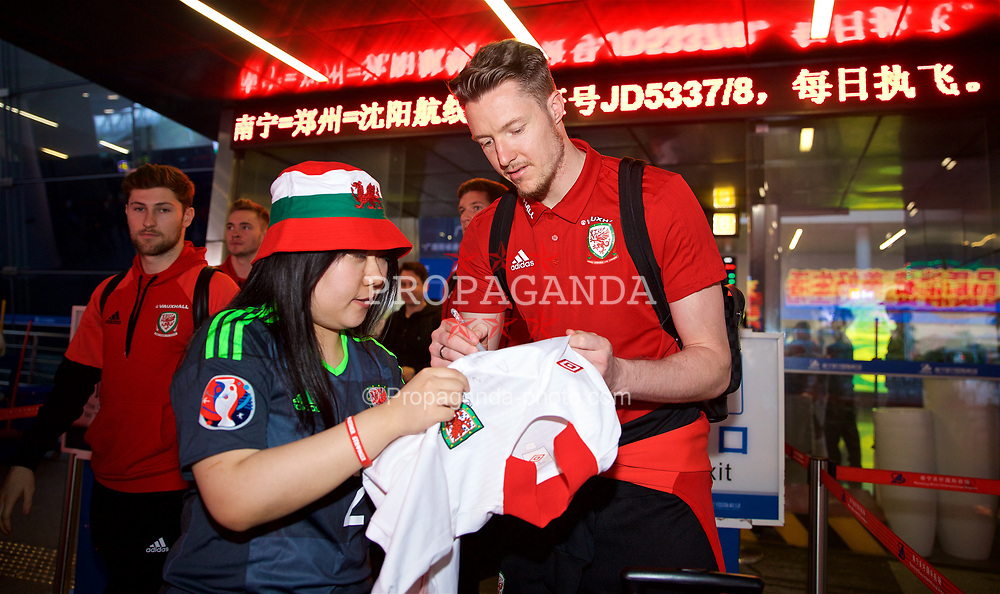 NANNING, CHINA - Monday, March 19, 2018: Wales goalkeeper Wayne Hennessey signs a shirt for a supporter as the team arrive at Nanning International Airport for the 2018 Gree China Cup International Football Championship. (Pic by David Rawcliffe/Propaganda)