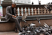 A man wearing a grey suit feeds seeds to a large group of pigeons in the city square on 18th August, 2021 in Leeds, United Kingdom.