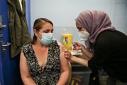 © Licensed to London News Pictures. 01/05/2021. London, UK. A NHS Covid-19 vaccinator administers the Oxford/AstraZeneca vaccine to a woman at a vaccination centre in Haringey, north London. In the UK, over 34.2 million people have received a first dose and almost 14.5 million are fully vaccinated. People aged 40and over can now book their appointments through the national booking website as part of the next phase of the government's vaccination programme. <br /> <br /> ***Permission Granted*** <br /> <br /> Photo credit: Dinendra Haria/LNP