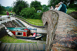 Visitors watch a boat exit the bottom lock at Foxton Locks on the Grand Union Canal, Leicestershire, England, UK.