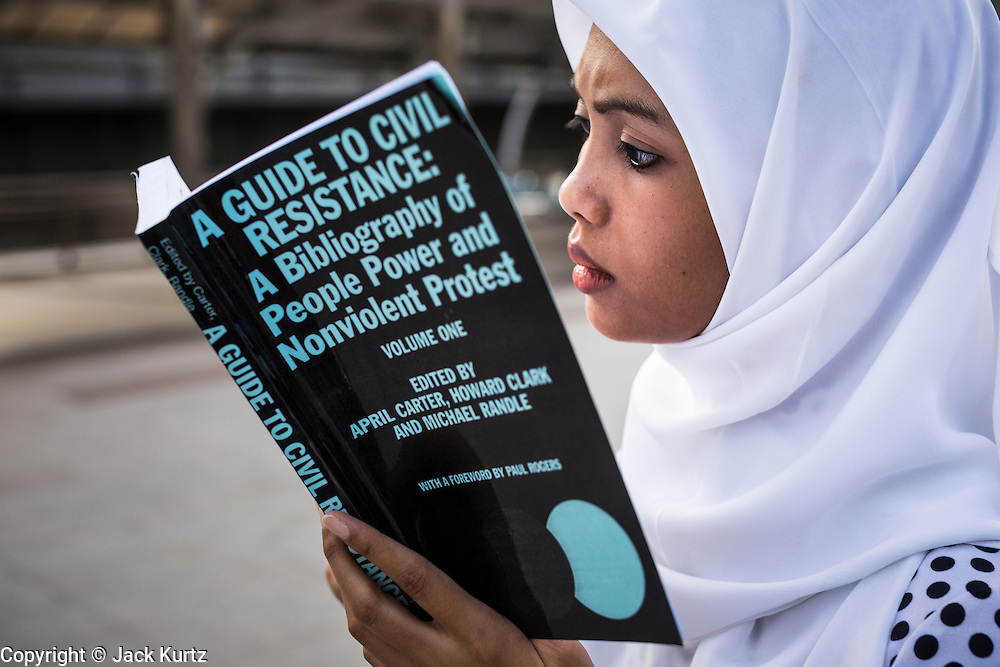 """29 MAY 2014 - BANGKOK, THAILAND: A woman reads """"A Guide to Civil Resistance"""" during a protest against the Thai coup Thursday. About eight people gathered at the Chong Nonsi intersection in Bangkok to silently read George Orwell's """"1984"""" and other books about civil disobedience. The protests are based on the """"Standing Man"""" protests that started in Turkey last summer. Authorities made no effort to stop the protest or interfere with the people who were reading.   PHOTO BY JACK KURTZ"""
