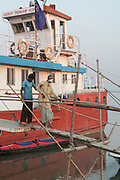 Bangladesh, Jamuna River, (called the Brahmaputra River in India) near the town of Gaibanda. This is the boat based Friendship non-profit organization (NGO), who provide health care and vocational traing  for locals. A local man who has recently had a cataract opertion on his eyes is assistant as he departs from the hospital ship.