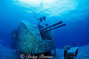 diver swims past 76.2 mm cannons on wreck of <br /> Russian missle frigate, Destroyer 356, <br /> renamed MV Capt. Keith Tibbits,<br /> Cayman Brac ( Caribbean Sea )   MR 282