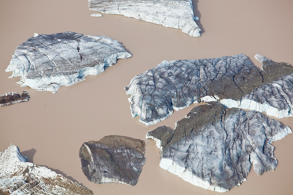 Aerial view of calved icebergs floating in the terminal lake of the Nizina Glacier from a Wrangell Mountain Air bush plane flight in Wrangell-St. Elias National Park, Alaska.