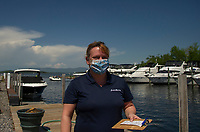 Sporting a Lake Winnipesaukee face mask Stephanie Mobbs assists boaters at the gas dock in Mountain View Yacht Club on Wednesday afternoon.  (Karen Bobotas/for the Laconia Daily Sun)