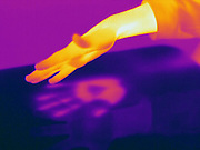 Thermogram of a hand and thermal shadow.  The hand was placed on the desk top for a few minutes, then removed.  The warm area on the table is where the hand was placed.  The different colors represent different temperatures on the object. The lightest colors are the hottest temperatures, while the darker colors represent a cooler temperature.  Thermography uses special cameras that can detect light in the far-infrared range of the electromagnetic spectrum (900?14,000 nanometers or 0.9?14 µm) and creates an  image of the objects temperature..