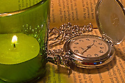 still life of an old style pocket watch, lid and chain with a candle on an open book