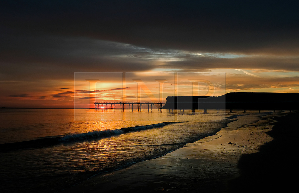 © Licensed to London News Pictures. <br /> 28/08/2017<br /> SALTBURN-BY-THE-SEA, UK.  <br /> Sunrise over the pier and cliffs at Saltburn-by-the-Sea on Bank Holiday Monday.<br />   <br /> Photo credit: Ian Forsyth/LNP
