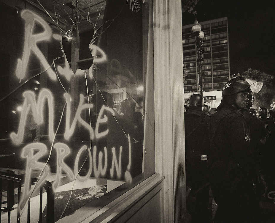 Police officers guard the Oakland storefronts from being further vandalized.