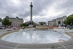 © Licensed to London News Pictures. 25/08/2021. London, UK. A maintenance team clean the large drained fountains in TRAFALGAR SQUARE during the Summer holidays. Photo credit: Ray Tang/LNP