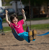 Laughing 3 year old girl enjoys swinging at a playground in the summer.