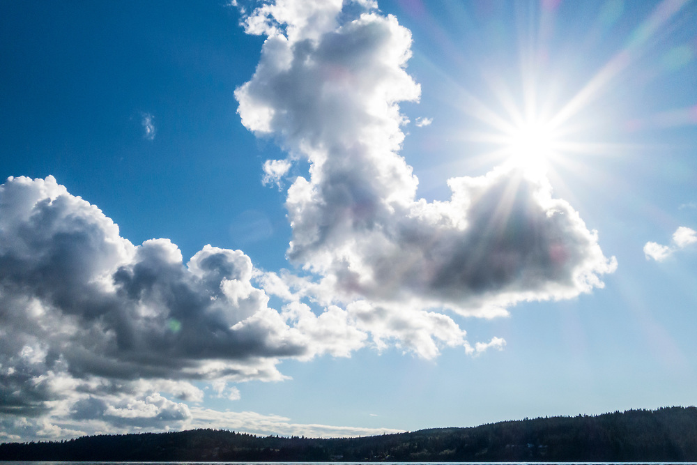 The sun peaking over some white puffy clouds over Whidbey Island, Washington, USA.