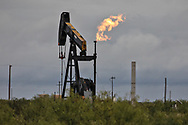 Pump jack and a flare in  Coyanosa , Texas in the Waha oil field in the Permain Basin.