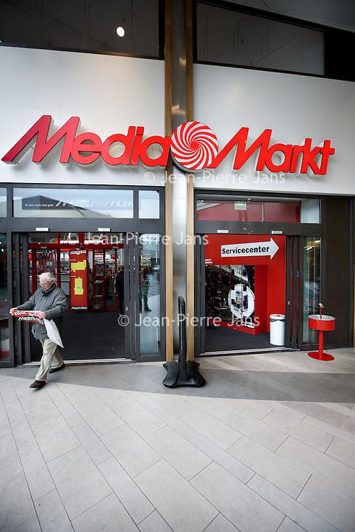 Nederland, Amsterdam , 25 februari 2011..Bezoeker verlaat met lege handen de Mediamarkt in amsterdam Noord..Client leaves electronics shop Mediamarkt without buying, just the deals folder.