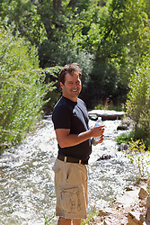 man holding a water bottle by a river