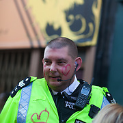 A Metropolitan police officer with love hearts painted on his cheeks and uniform. The Notting Hill Carnival has been running since 1966 and is every year attended by up to a million people. The carnival is a mix of amazing dance parades and street parties with a distinct Caribbean feel.
