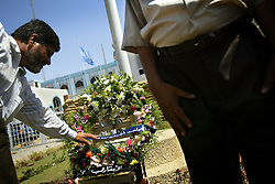 Members of the nine Nissan councils (local councils in Baghdad) place a wreath in front of the Canal Hotel in Baghdad, Iraq on Aug. 21, 2003. Earlier in the week a cement truck packed with explosives detonated outside the offices of the UN headquarters in Baghdad, Iraq, killing 20 people and devastating the facility in an unprecedented suicide attack against the world body. At least 100 people were wounded.