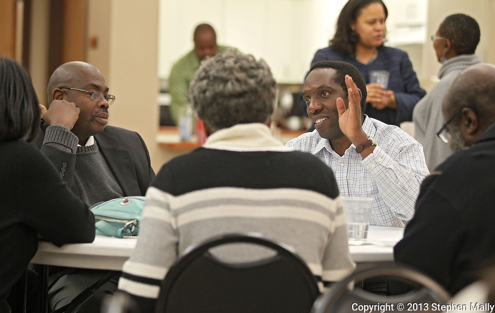 Primus Mutasingwa (right), of Cutting Edge Safaris, talks with people during a meal at a meeting of RED-I at the African American Museum of Iowa in Cedar Rapids on Thursday, December 12, 2013.