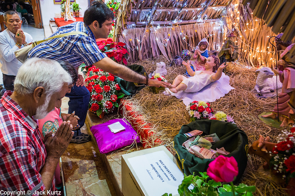 24 DECEMBER 2013 - BANGKOK, THAILAND: People pray in front of a doll that represents the Baby Jesus in a nativity scene during Christmas services at Holy Redeemer Church in Bangkok. Thailand is predominantly Buddhist but Christmas is widely celebrated throughout the country. Buddhists mark the day with secular gift giving but there are about 300,000 Catholics in Thailand who celebrate religious Christmas. Catholics first came to Thailand (then Siam) in 1567 as chaplain for Portuguese mercenaries in the employ of the Siamese monarchy. There has been a continuous Catholic presence in Thailand since then.   PHOTO BY JACK KURTZ