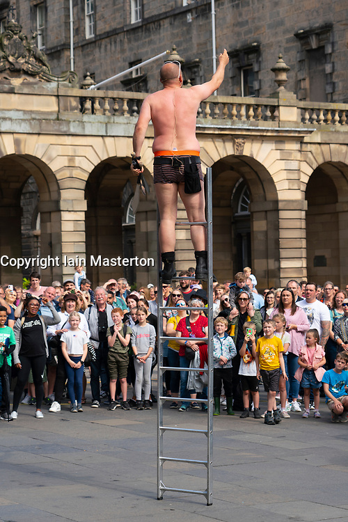 Edinburgh, Scotland, UK. 22nd August 2021. Street performer entertains large crowd on the Royal Mile in Edinburgh Old Town during the Edinburgh Fringe Festival 2021. Good weather brought out more visitors to the city this weekend and more stages have been allocated to street performers on the popular Royal Mile. Iain Masterton/Alamy Live News.