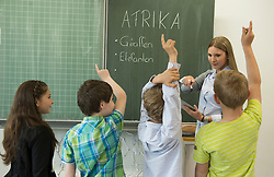 Female teacher teaching students in classroom with digital tablet, Munich, Bavaria, Germany