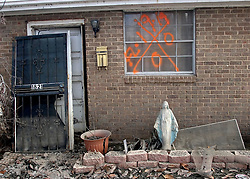 01 October, 05.  New Orleans, Louisiana. Lower 9th ward. Hurricane Katrina aftermath. <br /> The remnants of the lives of ordinary folks, now covered in mud as the flood waters recede.  A statue of the Virgin Mary stands outside a storm ravaged home.<br /> Photo; ©Charlie Varley/varleypix.com