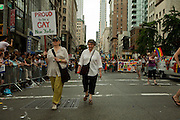 "Two women, one bearing a sign saying ""Proud to be a gay New Yorker,"" marching in the 2011 Pride Parade on New York's Fifth Avenue."