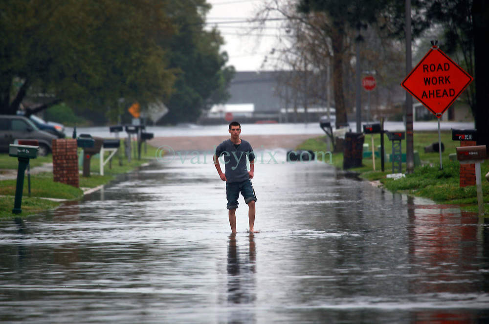 22 March 2014. Marrero, Louisiana. <br /> A man stands in the middle of a flooded street as storms sweep through the region flooding low lying streets.<br /> Photo; Charlie Varley