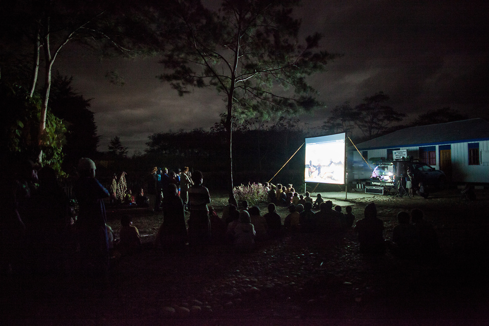 Children and parents from the Husoak village outside of Wamena watch an educational movie on HIV/AIDS.  The film uses the local dialects and also entertaining and informative attracting hundreds of villagers to the showings.<br /> <br /> Perhaps one of the most efficient ways to promote awareness and educate the public on HIV/AIDS is by playing informative movies at open forums.  In Wamena, YUKEMDI, a local NGO run by indigenous Papuans, plays an educational movie in rural villages that uses the local dialects and featuring native Papuans.  The film is both entertaining and informative often attracting hundreds of villagers to the showings.  Villagers receive additional information after watching the movie and are encouraged to ask questions in order to promote communication and open discussions.  However, these screenings are not conducted as often as they should be despite their effectiveness and demands from village elders.  YUKEMDI is unable to reach and provide HIV/AIDS education to rural villages because they have insufficient funding and support to cover the costs of fuel, transportation, and equipments for the movie screenings in remote communities.<br /> <br /> Better methods of education and more effective ways of delivering information on HIV/AIDS need to be implemented in Papua in order to effectively raise awareness and provide accurate and reliable information.  This is an essential step to educate and empower the public to make informed decisions and reduce their vulnerability to HIV infection.