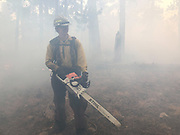 Thick smoke forces Larimer County Sheriff's Office firefighter Quinn de la Haye to pause from cutting along a fireline, October 24, 2020 as the East Troublesome Fire burns in the Rocky Mountain National Park. © 2020 William A. Cotton