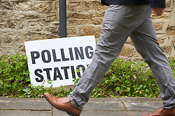 © Licensed to London News Pictures.  07/05/2015. OXFORD, UK. A man walks past a polling station sign in Oxford on the day of the 2015 General Election. Photo credit: Cliff Hide/LNP