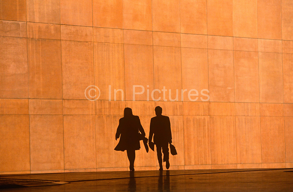 We see four office workers silhouetted against the large orange wall of the Credit Lyonnais Bank at Broadgate in the City of London, UK. The two figures are reduced to black shapes and without detail that may identify them or their clothes, are hurrying in the same direction, carrying a bag or briefcase but the feeling of rushing business is seen and their scale is ambiguous because we don't know how close or far away they are from each other. This is due to telephoto lens foreshortening. Some therefore look giants and some appear tiny. Broadgate Estate is a large, 32 acre (129,000 m²) office and retail estate in the City of London, owned by British Land and managed by Broadgate Estates. It was originally built by Rosehaugh and was the largest office development in London until the arrival of Canary Wharf in the early 1990s.