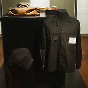 """TREVISO, ITALY - NOVEMBER 12:  A general view of some of the personal objects belonging to the last Emperor Pu Yi relating to his imprisonment,prison clothes, a royal seal, a bag, a cup and a plate with the inmates number, shown to the public for the very first time on November 12, 2011 in Treviso, Italy.  The exhibition called, """"Manchu, The Last Emperor"""" will stay open until the 13th May 2012.  (Photo by Marco Secchi/Getty Images)"""