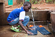 A young boy washes his trousers at the AFCIC centre in Thika, Kenya. AFCIC - Action for children in conflict, help children who have been affected by various forms conflict or crisis.