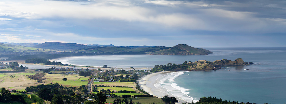 High-angle panoramic view of Karitane, Otago, New Zealand, with Cornish Head in the background.  Sunlight breaks through the clouds to highlight Karitane.