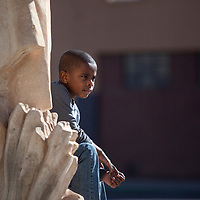 Jarvis K. Vaughn III, sits on a statue of Chief Manuelito in downtown Gallup Monday waiting for the parade honoring Martin Luther King Jr. to commence.