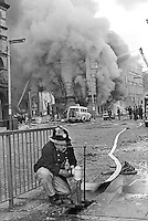 Firemen tackle blaze following Provisional IRA 500 lb bomb attack on the RUC police station, Musgrave Street, Belfast, N Ireland. Adjacent buildings seemed to have suffered more damage than the actual police station. It was claimed the bomb attack was in retaliation for the death of IRA member Hugh Coney who was shot dead by a sentry during an escape attempt at the Maze Prison. Twenty nine other prisoners were captured within a few yards of the prison, and the remaining three were back in custody within 24 hours. 1974110604b.<br />