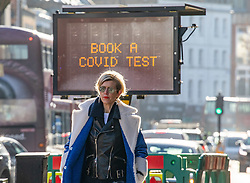 © Licensed to London News Pictures. 22/01/2021. London, UK. A member of the public walks past a Covid-19 information sign in Fulham South West London as the government downplays the idea of a universal £500 covid payment for those who self-isolate. A leaked government document suggested giving £500 to anyone who tested positive for coronavirus as death rates continue to rise in England. Photo credit: Alex Lentati/LNP