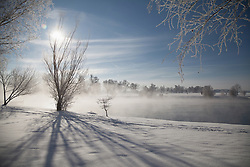 Sun shining over lake in winter, Eichenau, F¸rstenfeldbruck, Bavaria, Germany,