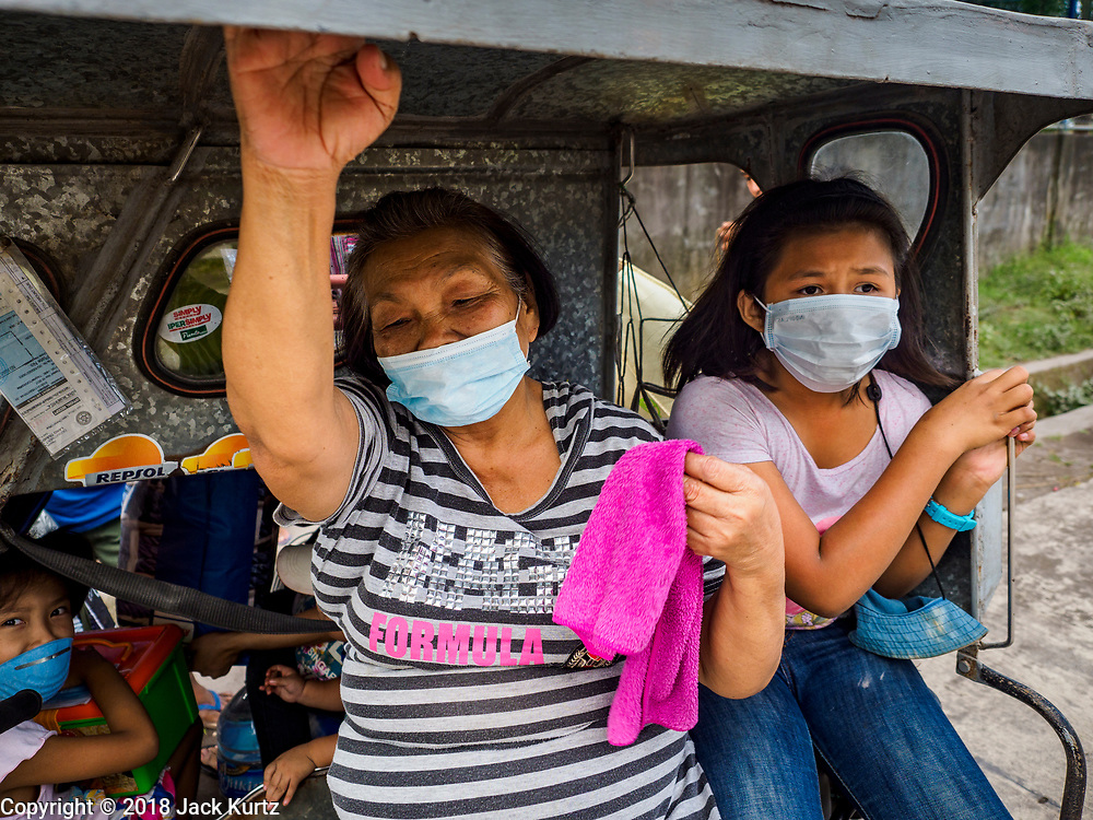 23 JANUARY 2018 - GUINOBATAN: ALBAY, PHILIPPINES: People in Guinobatan wear face masks for protection from an ash fall while they wait to be evacuated from their home. The Mayon volcano continued to erupt Tuesday, although it was not as active as it was Monday. There were ash falls in communities near the volcano. This is the most active the volcano has been since 2009. Schools in the vicinity of the volcano have been closed and people living in areas affected by ash falls are encouraged to stay indoors, wear a mask and not participate in strenuous activities.    PHOTO BY JACK KURTZ