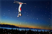 As night falls on Lake Tahoe a skier makes her way off the jump doing some tricks during the National Freestyle sking event. Picture taken at Heavenly Valley they hosted the event near the base lodge.