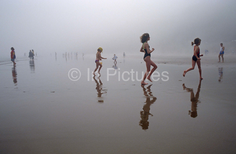 A mid-morning mist sweeps across the seafront's South Beach at Scarborough, the seaside town in North Yorkshire. Kids run about on the wet sand, some leaping and some just carrying buckets of salt water for sandcastles elsewhere. With the freedom and open-space, children who perhaps live in bleak industrial towns in northern England can enjoy the fresh-air on this north-eastern coast. Their reflections are also seen on the shiny sand and although it appears to be as grim as their home may be, it is in fact a warm day but the daily sea fogs that roll across this beach, a microclimate exists and is unique to this area.