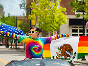 """28 JUNE 2020 - DES MOINES, IOWA: A woman with American and Mexican versions of the Pride Flag participates in the Capitol City Pride Parade in Des Moines. Most of the Pride Month events in Des Moines were cancelled this year because of the COVID-19 pandemic, but members of the Des Moines LGBTQI community, and Capitol City Pride, the organization that coordinates Pride Month events, organized a community """"parade"""" of people driving through the East Village of Des Moines displaying gay pride banners and flags. About 75 cars participated in the parade.    PHOTO BY JACK KURTZ"""