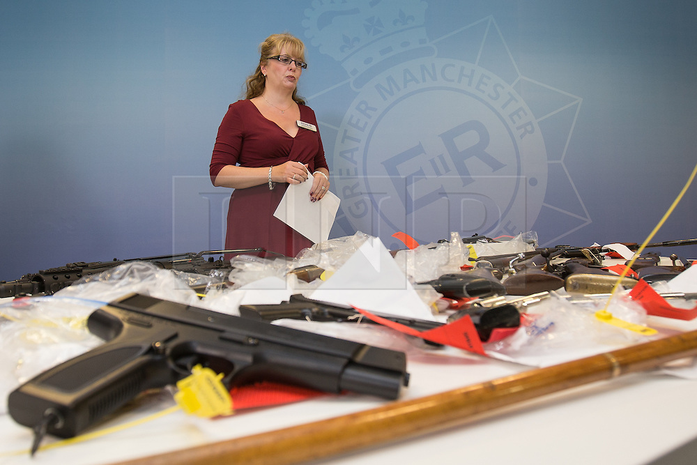 """© Licensed to London News Pictures . 07/08/2014 . Manchester , UK . Detective Chief Inspector Debbie Dooley of GMP's """" Xcalibre Task Force """" , which tackles gun-related crime , with some of the cache . Greater Manchester Police displays some of the cache of firearms and ammunition they collected during a two week firearms amnesty in July , at the force's North Manchester headquarters , this morning (7th August 2014) . GMP reports collecting 225 firearms and over 3000 rounds of ammunition during the fortnight amnesty of which , they say, over 80 of the weapons were illegally owned . Amongst the haul were rifles, shotguns , handguns and air weapons as well as imitation and antique firearms . Photo credit : Joel Goodman/LNP"""