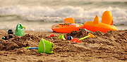 Children's toys scattered on the sand at the beach