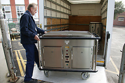 Logistic Operative loading hot food trolley onto van to be delivered to outlying wards at the Hospital,