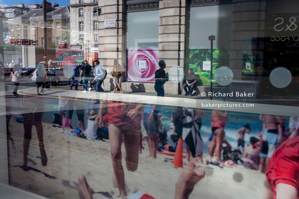 Londoners in autumn sunshine on the other side of the road, and in the foreground a poster featuring beach volleyball players, in Mayfair, central London, England.